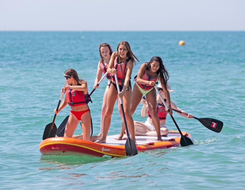 Girls paddle board in the sea on Brighton Beach