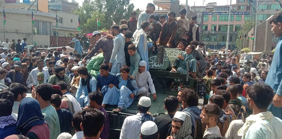 Taliban fighters and locals sit on an Afghan National Army humvee vehicle in Jalalabad