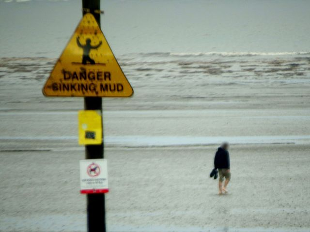 'Sinking Mud': a sign warning beach goers the dangers of getting too close to the tide