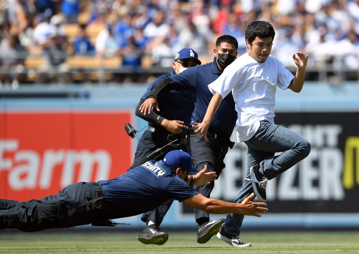 Watch hilarious moment young ball girl tackles pitch invader at LA Dodgers  baseball game as crowd go wild