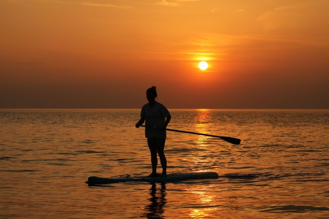 A woman soaks up the early sunshine from her paddleboard in Norfolk