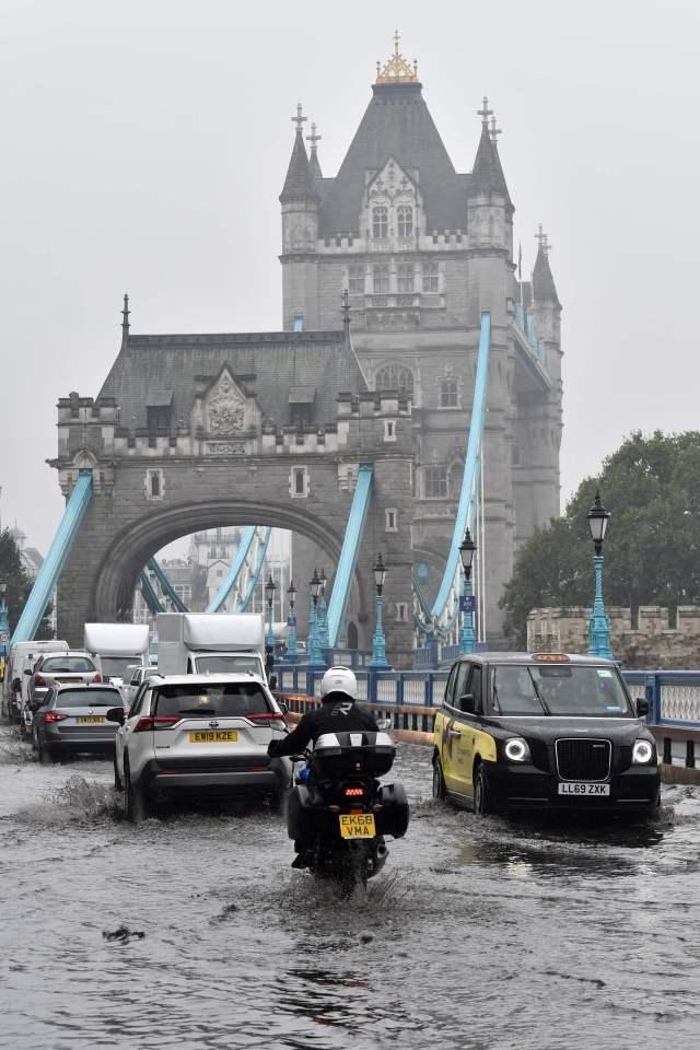 Motorists slowly made their way across the flooded bridge