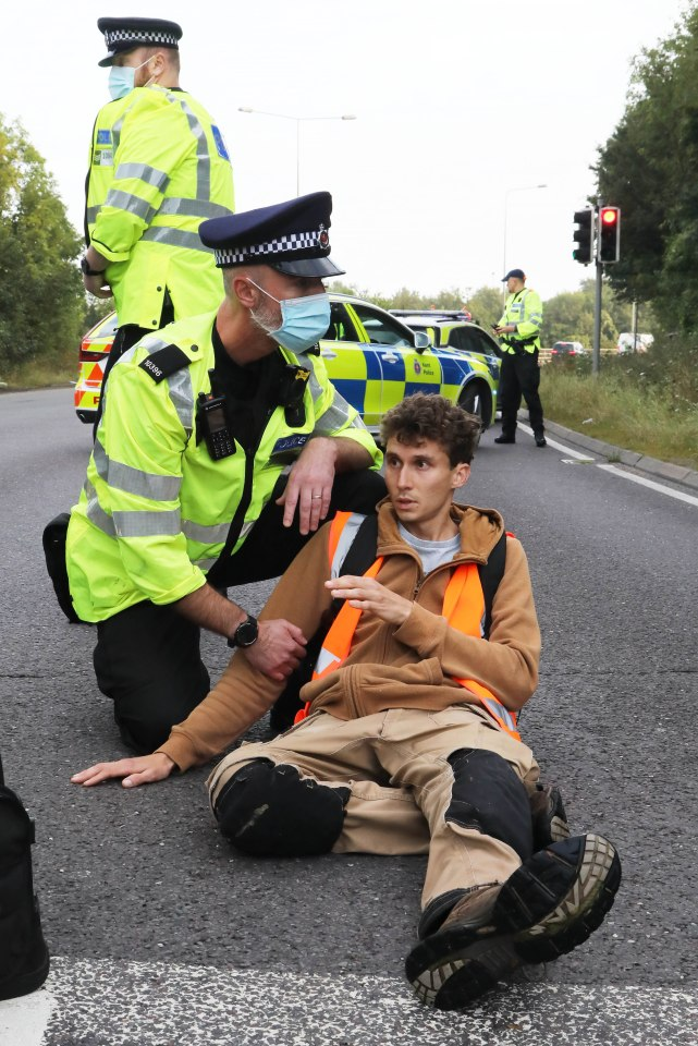 a man is lying on the road surrounded by police
