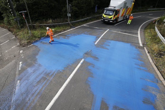 Highway England workers clean up after a blue paint is spilled on the motorway at Junction 9 of the M25 in Leatherhead