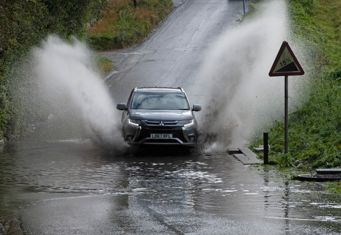 Cars run through flood waters in south east London