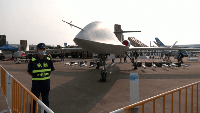 A security member stands next to a CH-6 high-altitude, long-range drone