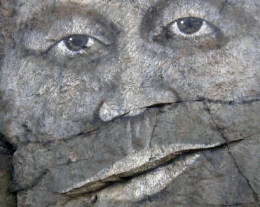 Painted stone face with brown eyes