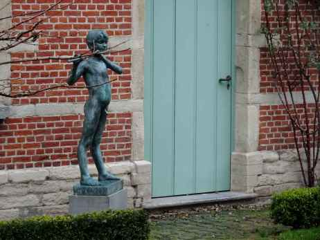 Child playing flute in the garden of the De Cellekens art studio