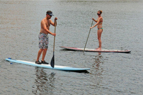 man and woman on stand up paddle boards on flat water