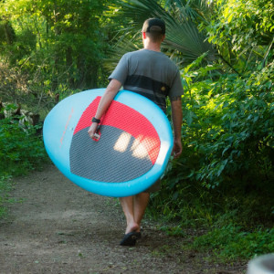 A man carrying a blue Journey SUP through a tree-lined path.