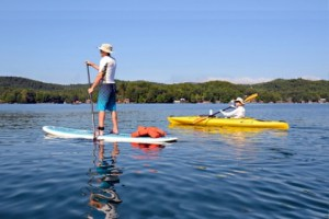 man on a paddle board next to a woman paddling a kayak in the ocean inlet