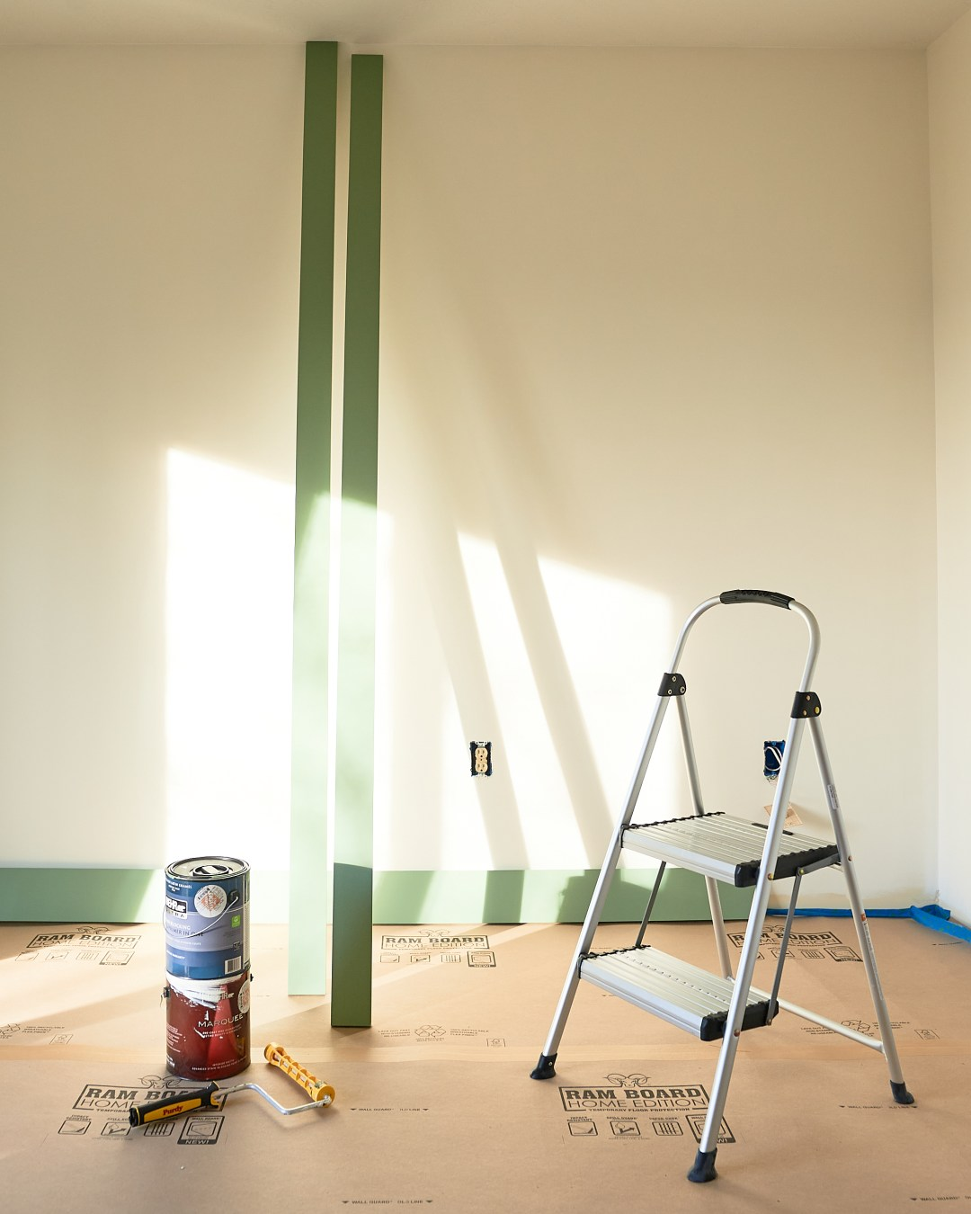 Warm white bedroom with green trim and paint supplies