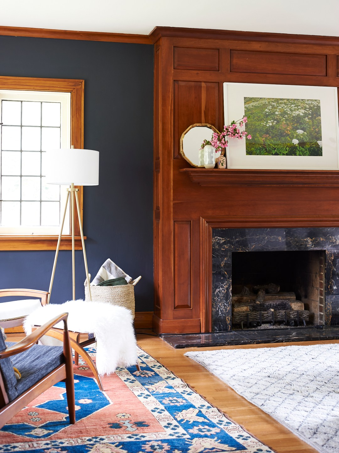 Traditional rug in living room with wood panel fireplace surround