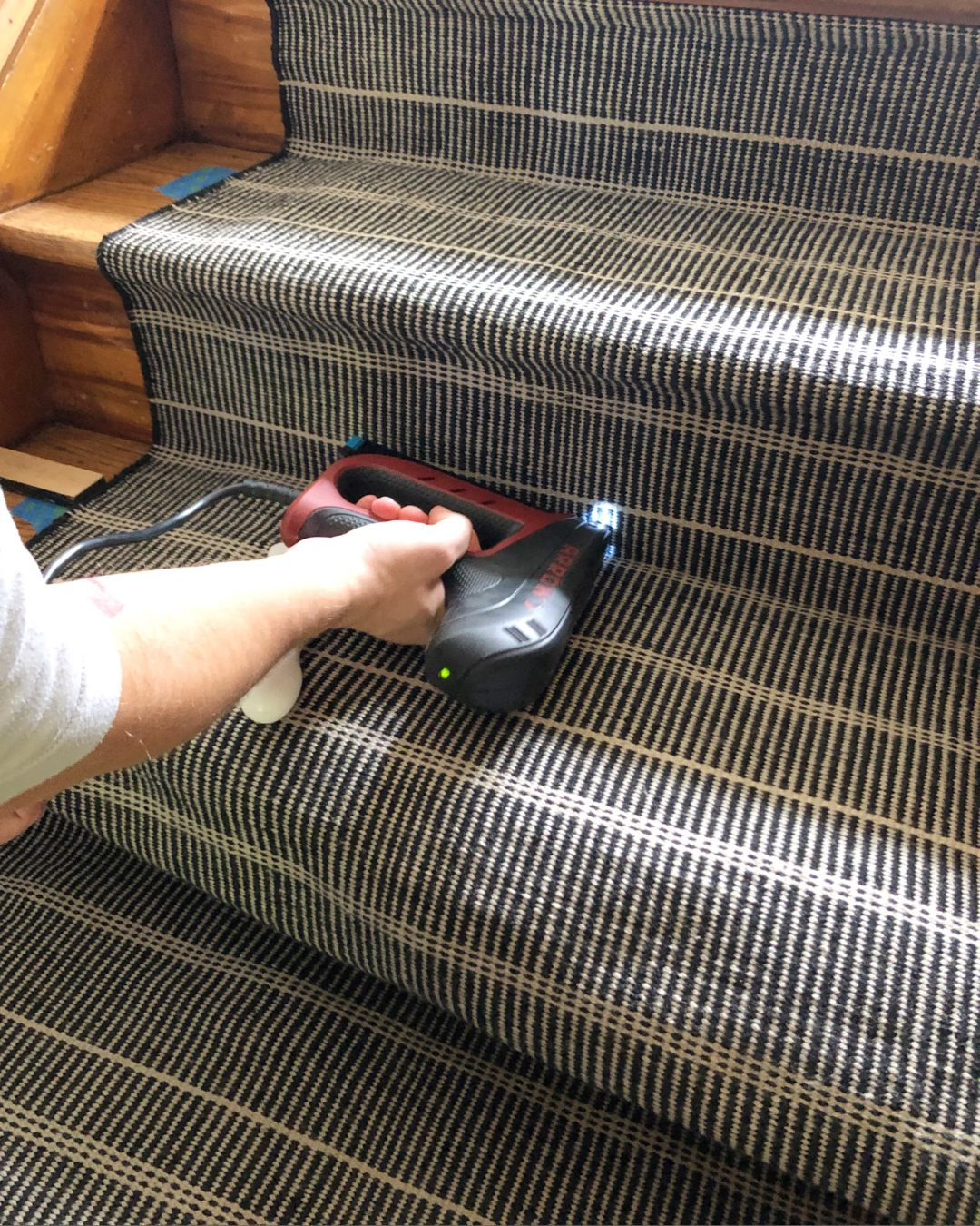 Using a staple gun to install a stair runner
