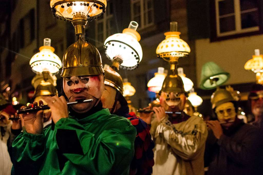 Members of a Clique wearing head lanterns while playing their piccolos in Morgestraich at the Basler Fasnacht