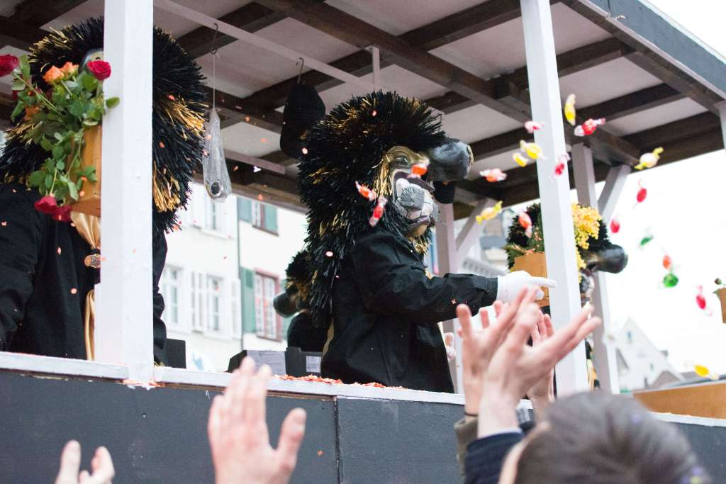 Waggis throwing candy to paraders at the Basler Fasnacht