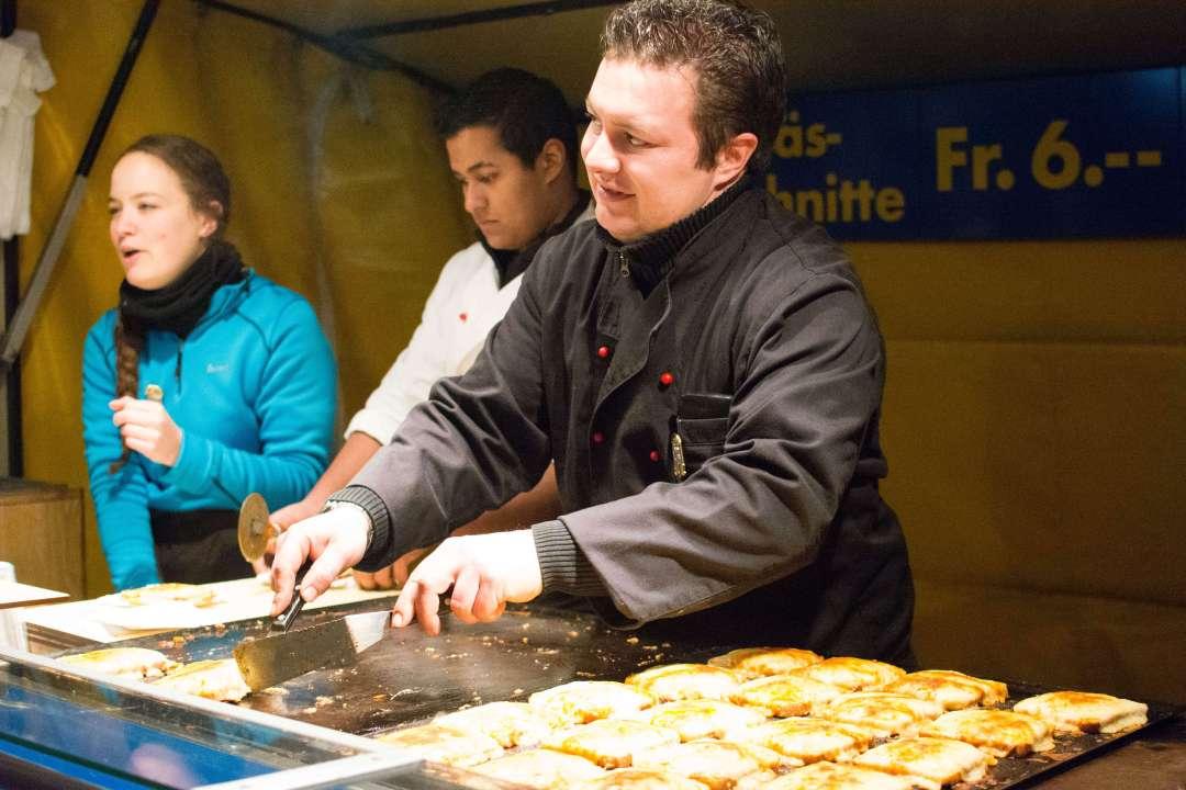 """Street vendor serving a popular cheese pie """"Chäschüechli"""" in Switzerland"""