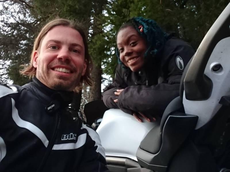 man and woman standing beside motorbike