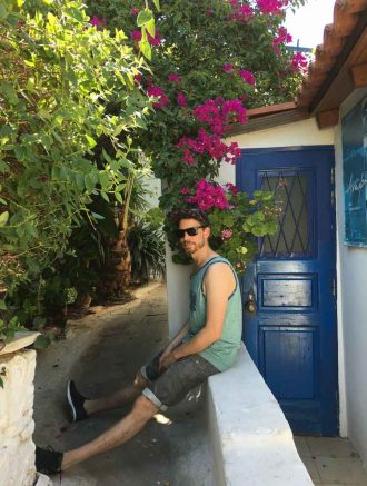 man sitting in front of a blue door