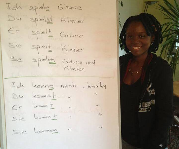 Girl standing by learning board with german words