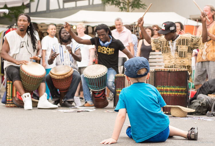 Boy watches African drummers as they perform