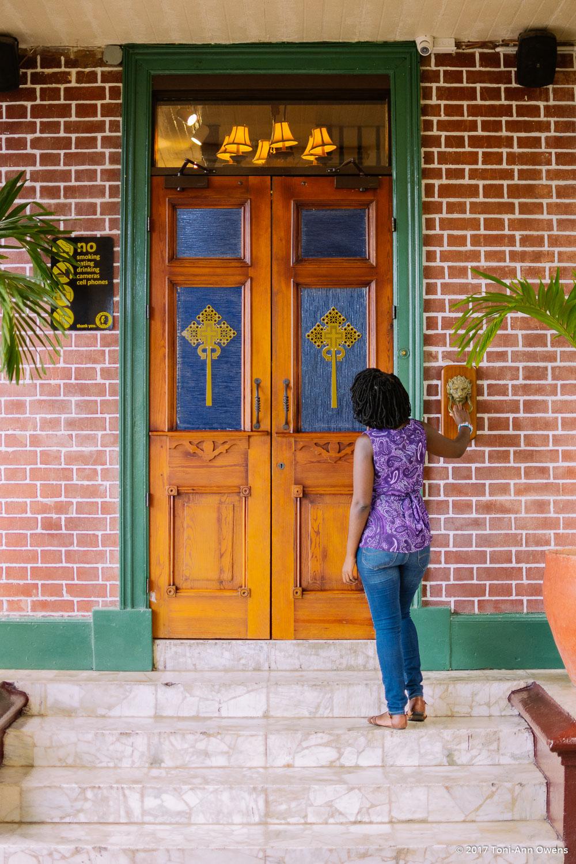 Girl Standing at the door of the Bob Marley Museum