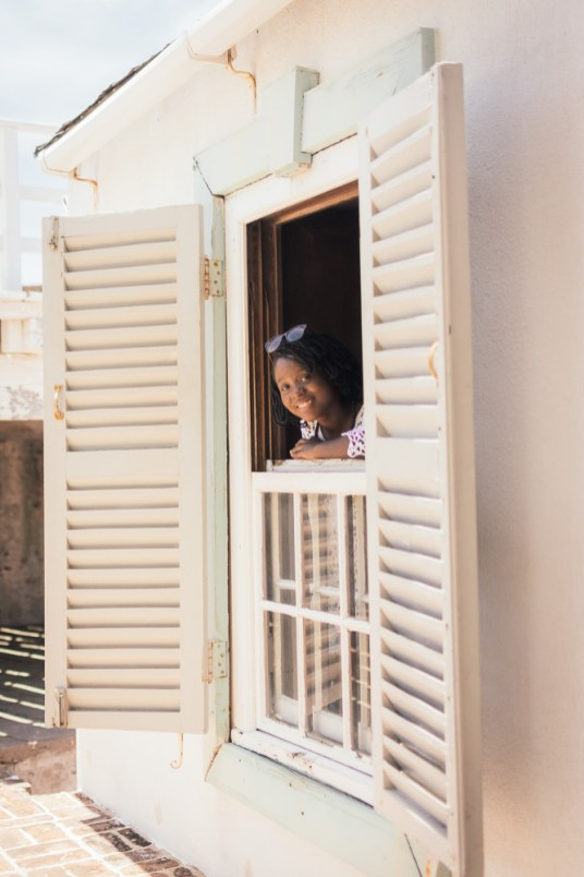 Girl Looking Out a Window at the Fort Charles Museum in Jamaica