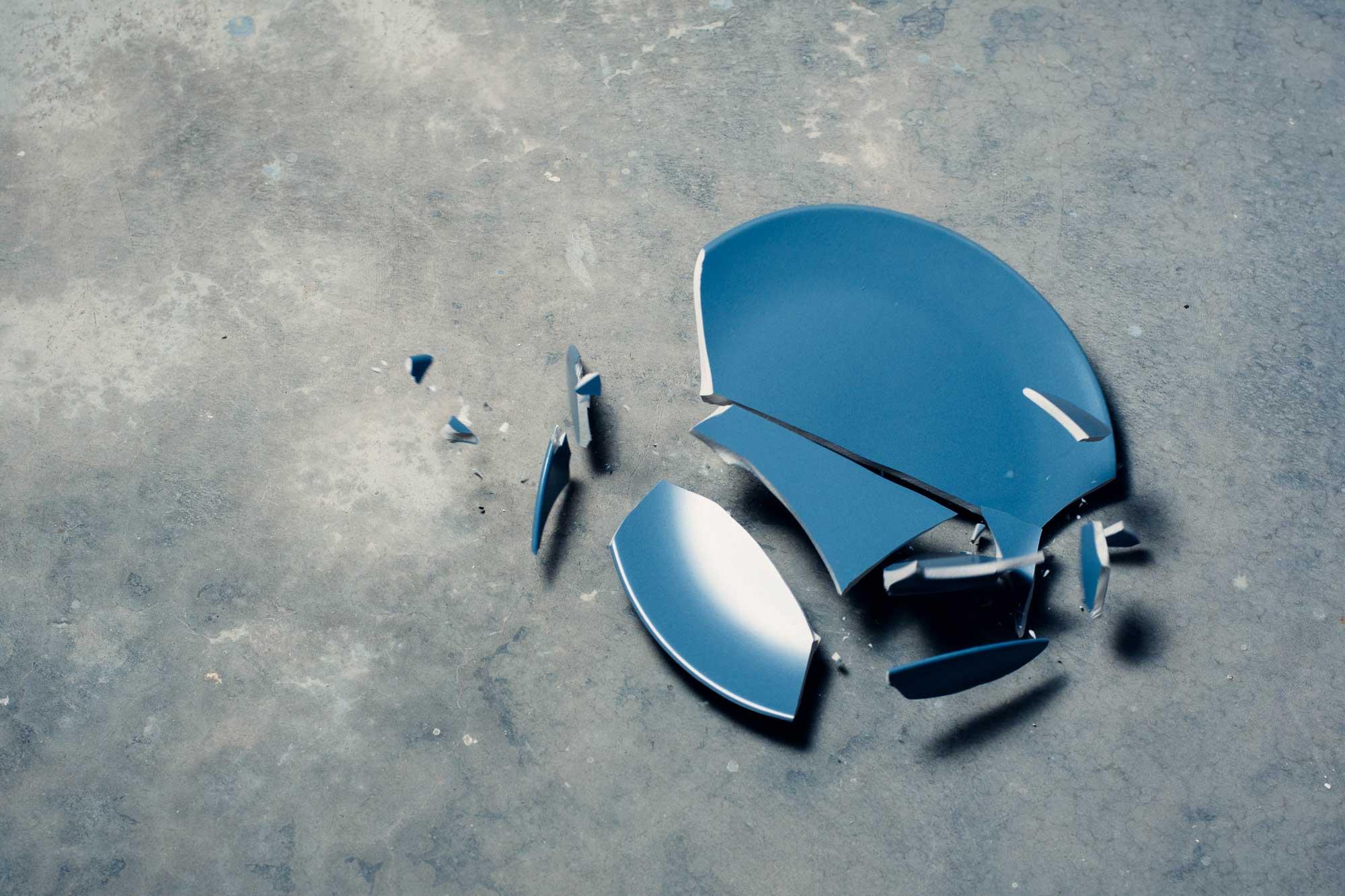 broken blue plate on concrete ground