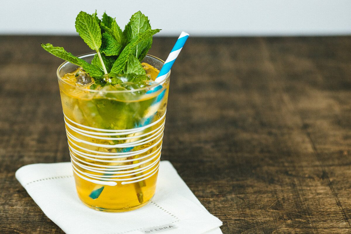 Mint Julep recipe by The Taste SF served in a zafferano glass with a paper straw
