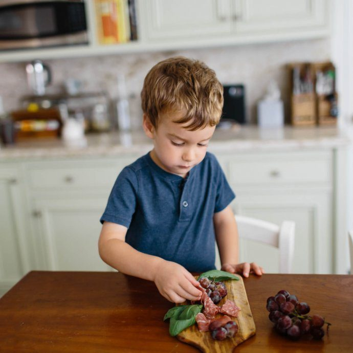 Charcuterie lunch ideas for kids including cheese, crackers, grapes, and meats