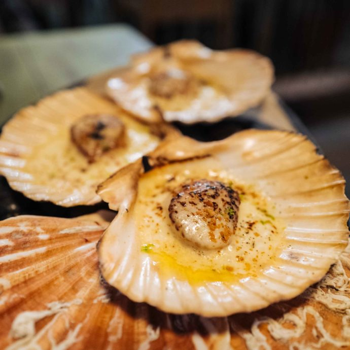 Don't miss the aged Parmigiano Reggiano foam topped grilled scallops served in their shells, in this Geneva Peruvian Restaurant | thetastesf.com #geneva #food #switzerland #scallops #travel
