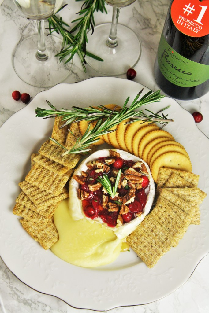 Warm, gooey baked brie topped with tart cranberry sauce, roasted pecans, honey and rosemary. A truly classic appetizer served up for the holidays