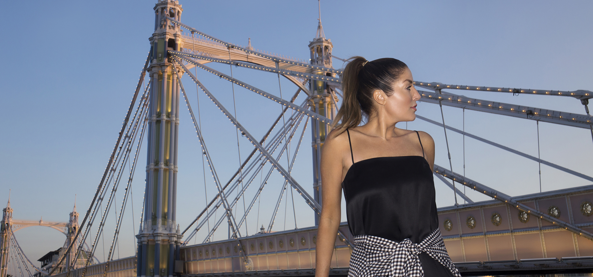 Taylor in a black dress standing in front of a bridge