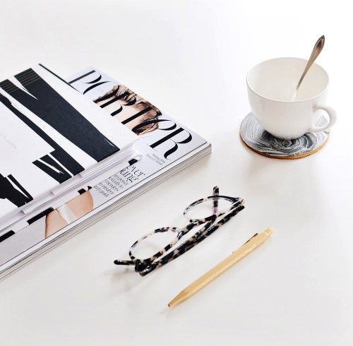 notebook, magazine and tea cup and eye glasses