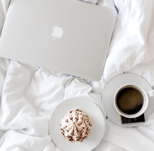 lap with coffee and cupcake on bed with white sheets