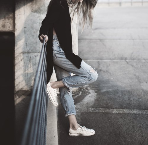 girl leaning on fence wearing converse blue jeans and black sweater