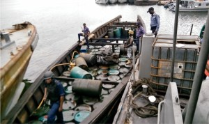 Officers of Nigerian Navy Ship (NNS), Pathfinder, Port Harcourt, guarding wooden boats loaded with 160 drums of illegally refined diesel which they siezed in Port Harcourt, recently.