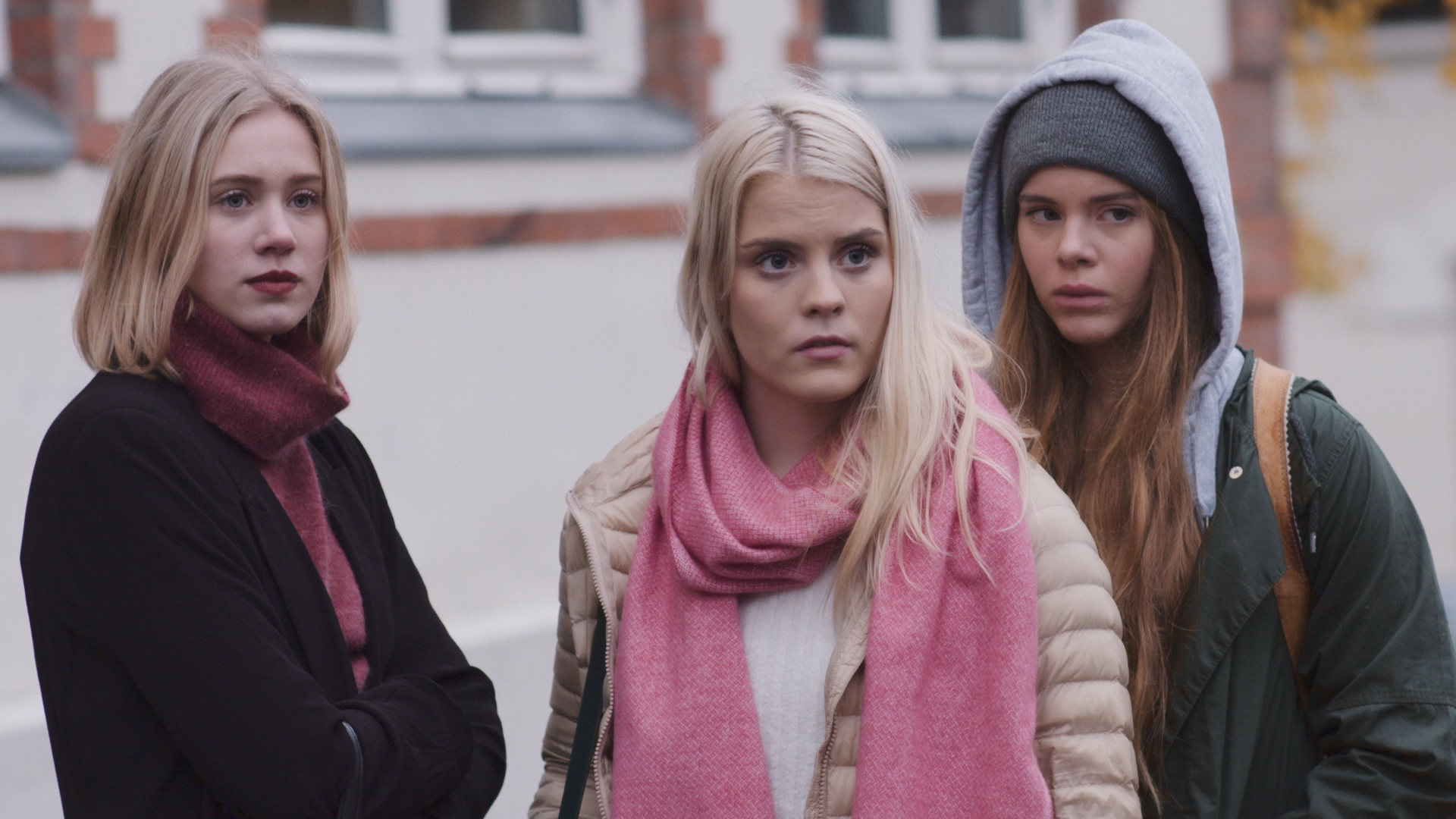 SKAM Norway. Noora, Vilde, and Eva, three teenage girls wearing coats and scarves, are standing outside school. Eva is standing just behind the other two with her jacket hood up, looking wary. Vilde and Noora are looking in the same direction, with stern expressions.