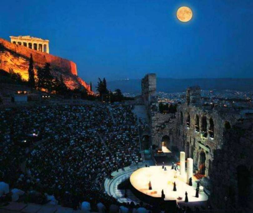 Summer Festivals in Greece: Athens and Folegandros. Stunning capture of the ancient theatre of Herodion during a performance with a full moon gracing the Acropolis.
