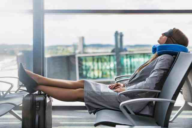 A business woman sleeping in an airport. A comfortable pillow is the best air travel accessories