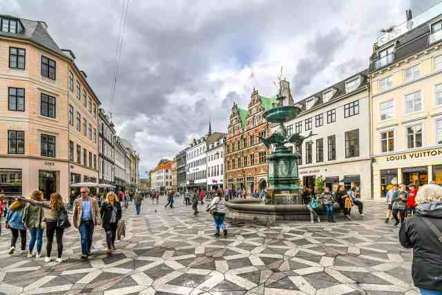 Tourists wander the Stroget shopping district, checking what to see in copenhagen, near the Stork Fountain, the longest pedestrian street in the world, in the City Centre of Copenhagen, Denmark. one of the top things to do in copenhagen