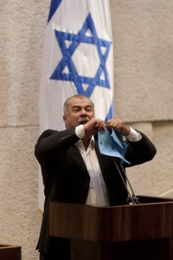 Knesset Member Mohammad Barakeh of the Hadash party tears thePrawer Plan during a plenum meeting in the Knesset, in Jerusalem, June 24, 2013. Arab Knesset members left the plenum Monday evening in protest. Photo: Flash 90