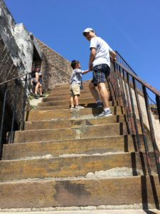 Tyler and Daddy climbing narrow stairs to the second level of Fort Pickens