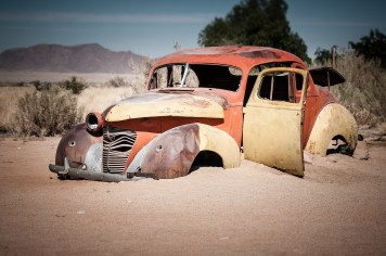 Old Car abandoned in the Namibia Desert and being swallowed by sand