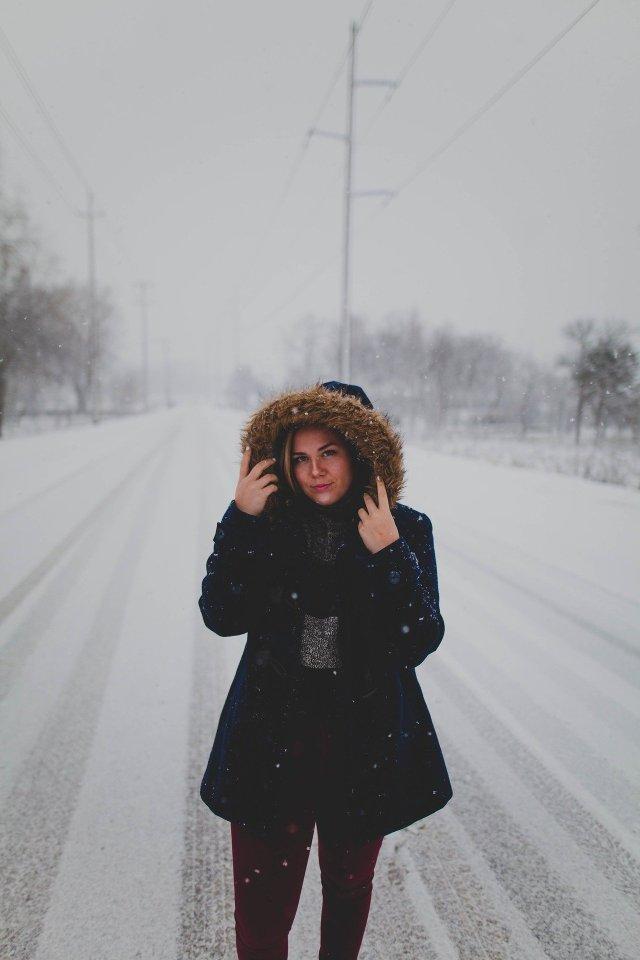 Woman in a winter coat walking on a snowy road