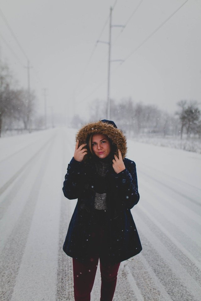 Woman in a winter coat walking on a snowy road