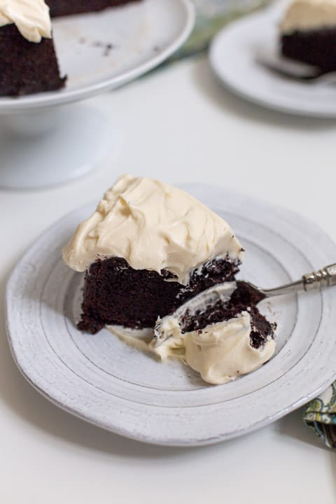 slice of guinness dark chocolate cake on a white plate with a fork slicing through