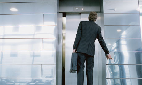 Businessman in front of elevator holding briefcase