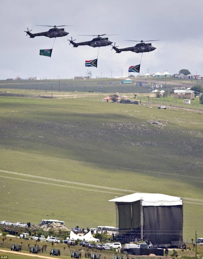 A nation in mourning: Three helicopters carrying South African flags fly over the burial site today as a much smaller crowd of mourners watched the great statesman laid to rest after ten days of official mourning