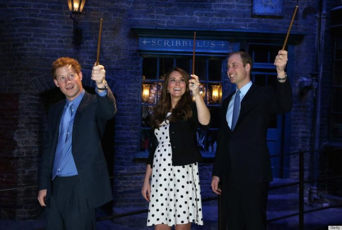 Prince Harry, Kate Middleton and Prince William raise their wands on the